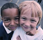 Black young child and a white young child in tight embrace
