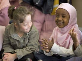 Girl with learning disabilities and young Muslim girl laughing together